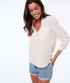 Blouse à rayures rose pale.