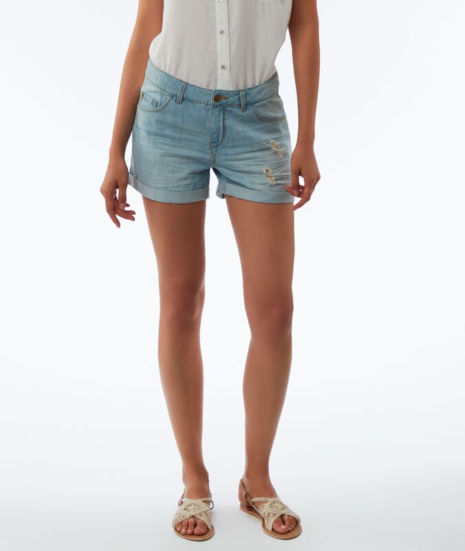 Torn jean shorts bleached light blue.